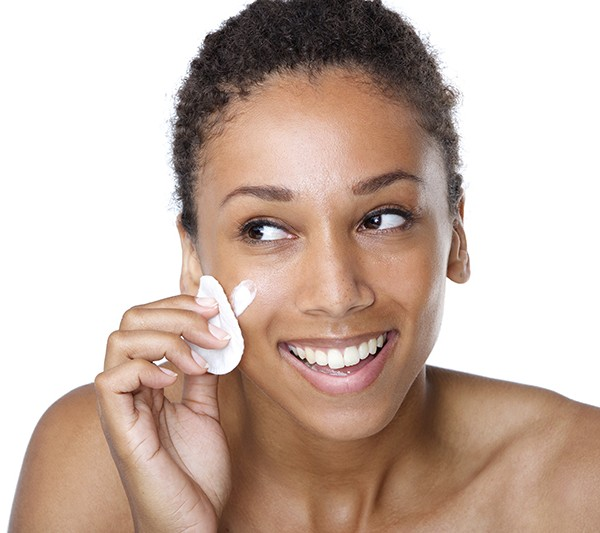Close up portrait of a smiling woman cleaning face with make up sponge